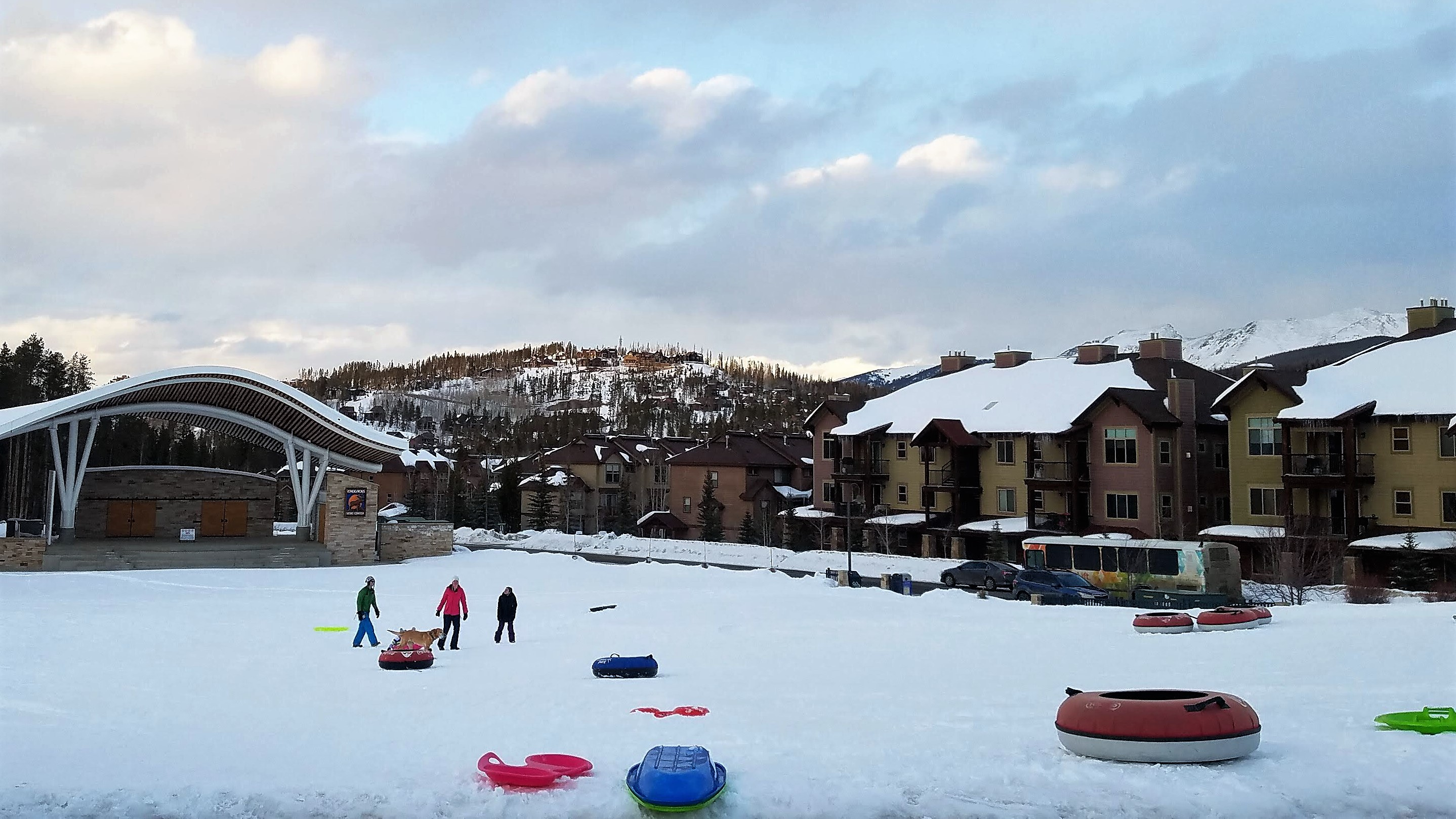 People playing in the snow with tall hotels in the background