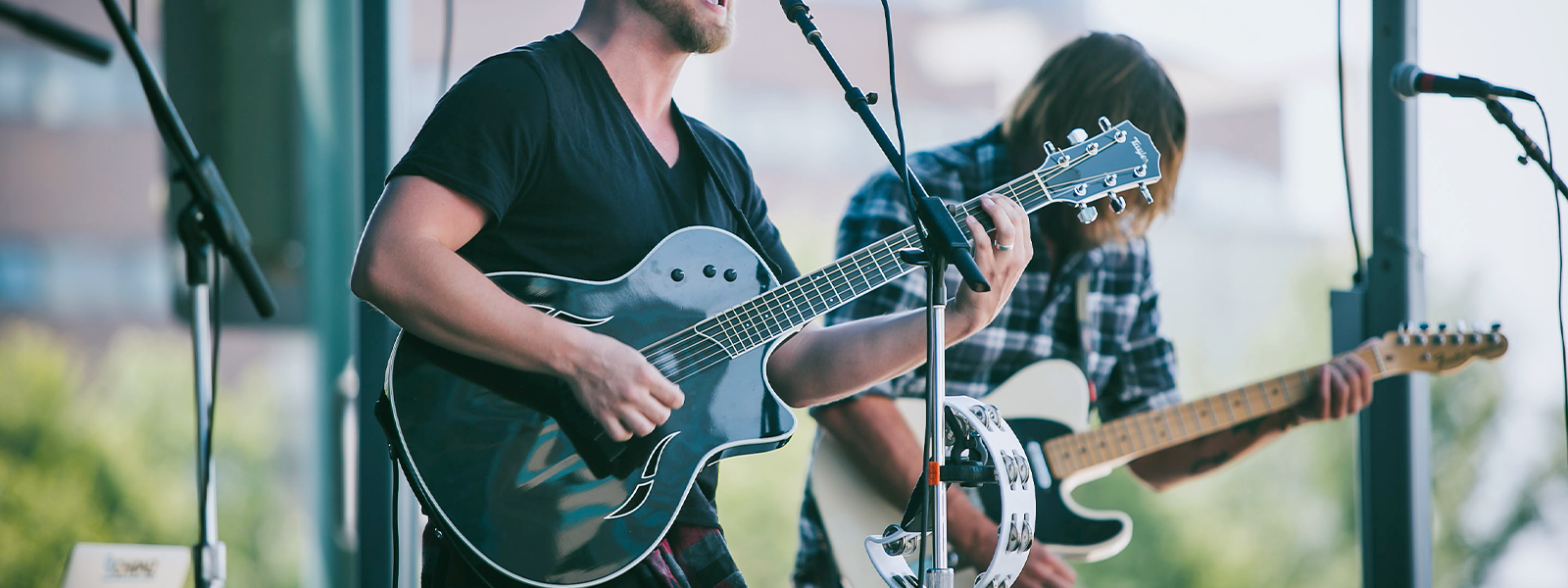 Two people playing guitars on stage