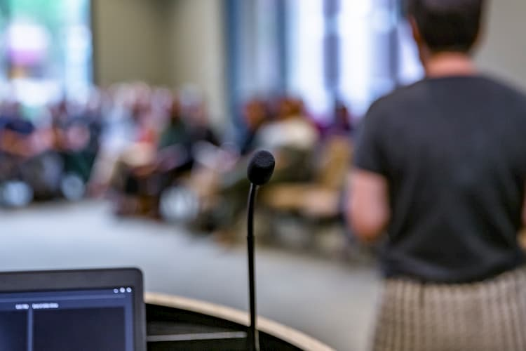 Picture of a microphone with a presentation going on in the background