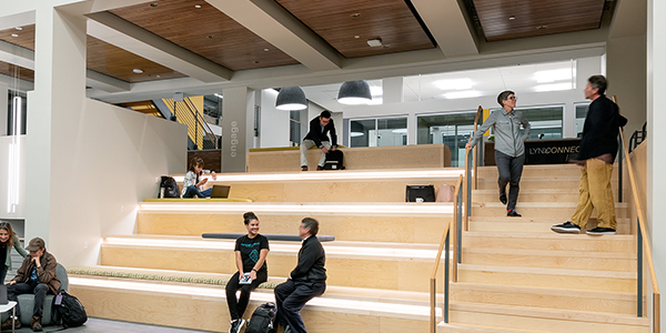 Students sitting on bench inside Student Commons Building