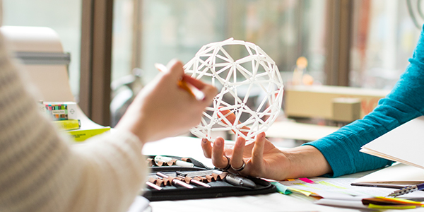 Hands holding small 3D-printed orb