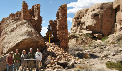 Group of students standing in front of partial stone structure