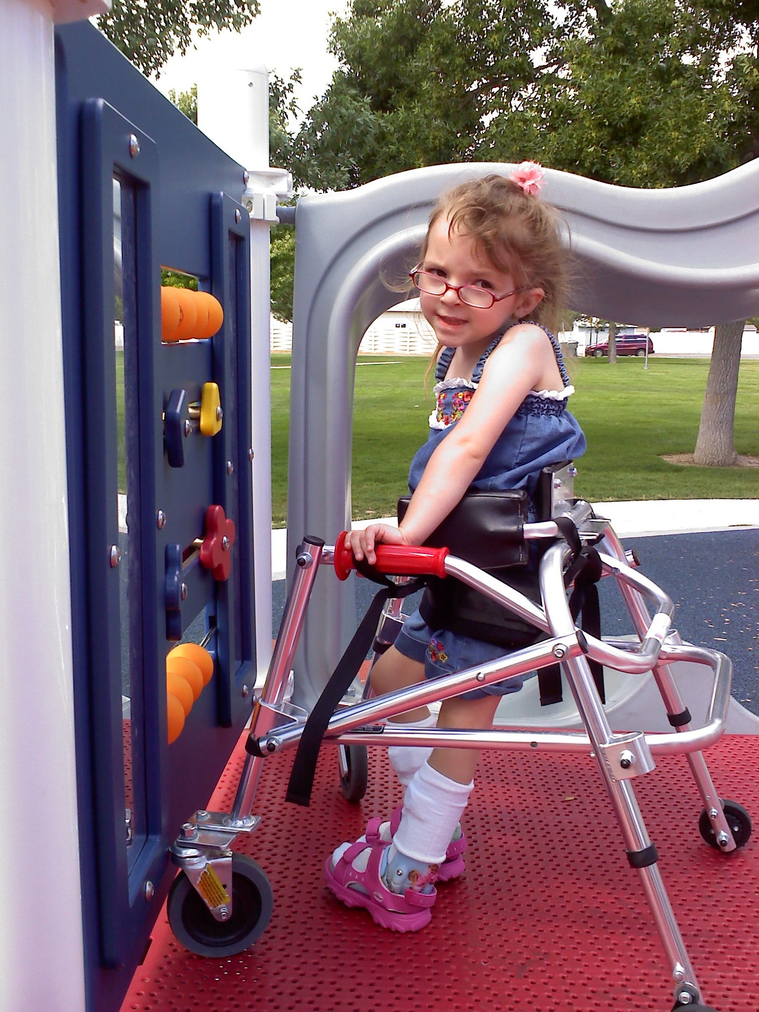 a young girl plays in a playground using her walker