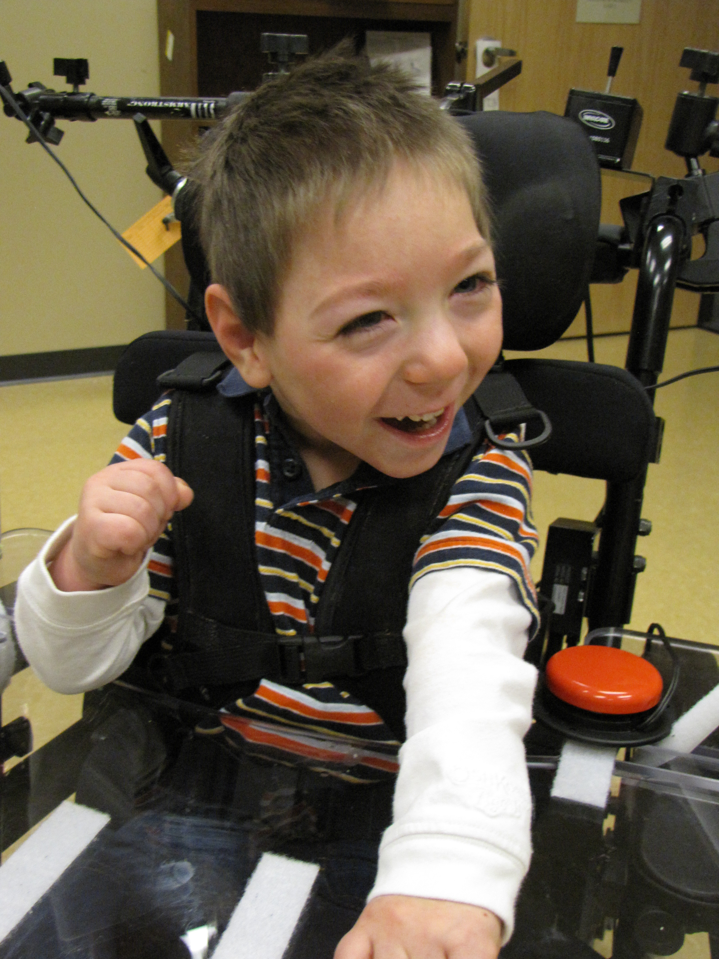 A child with cerebral palsy smiles while seated in his wheelchair. A tray and jelly bean switch are mounted to the chair.