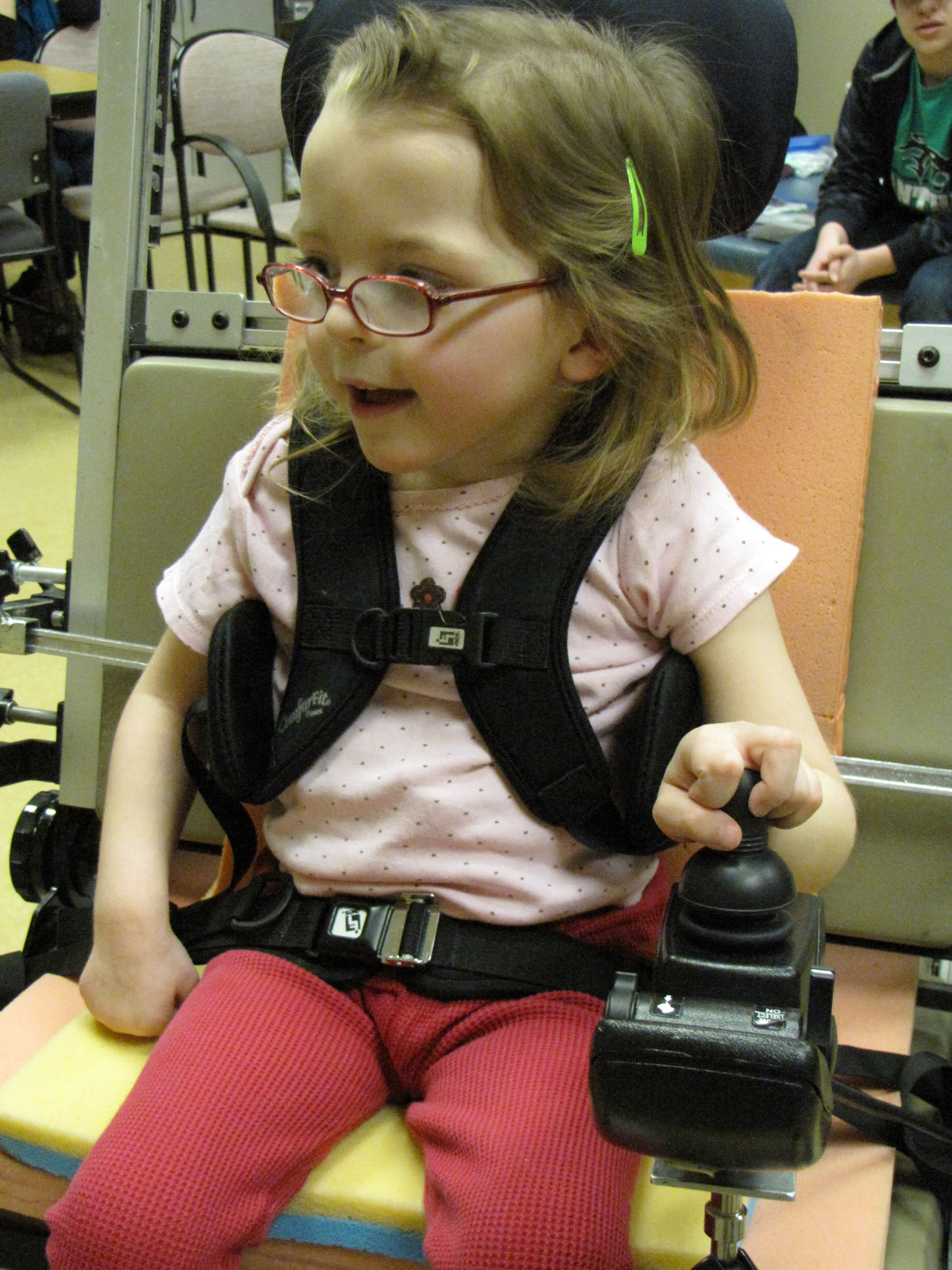 a young girl trials a new joystick for her power wheelchair