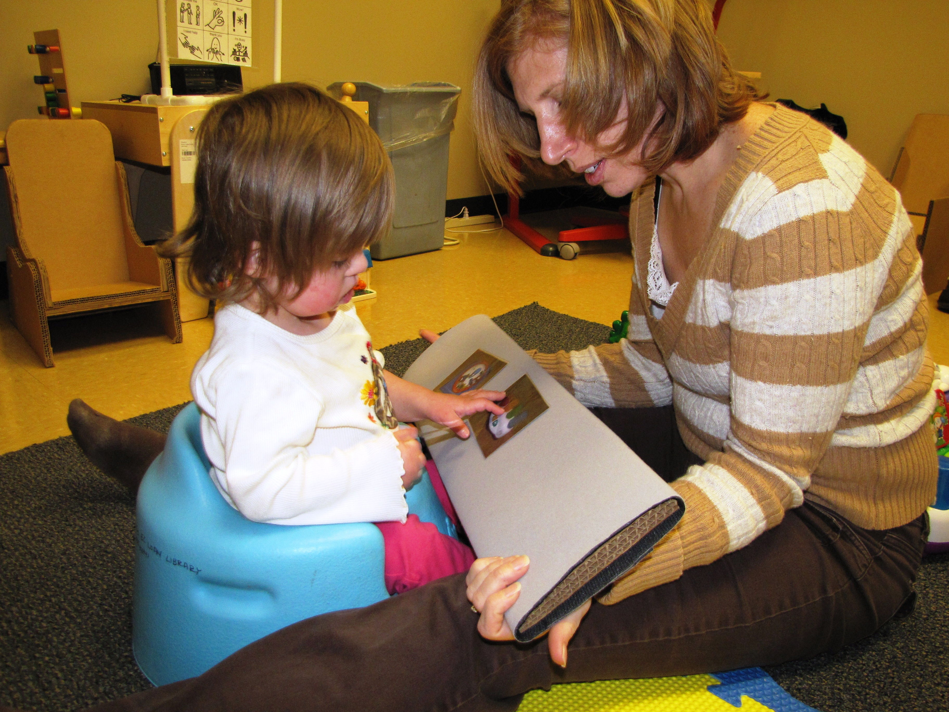 a toddler sits in an adapted seat interacts with a velcro storybook