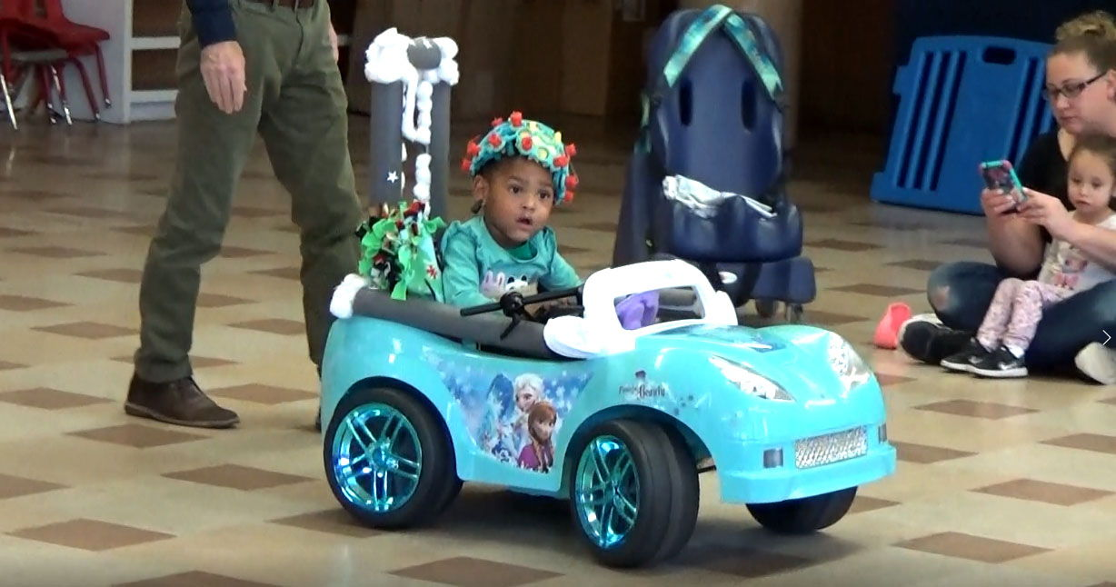 a young girl wears an e e g cap while driving an adapted toy car