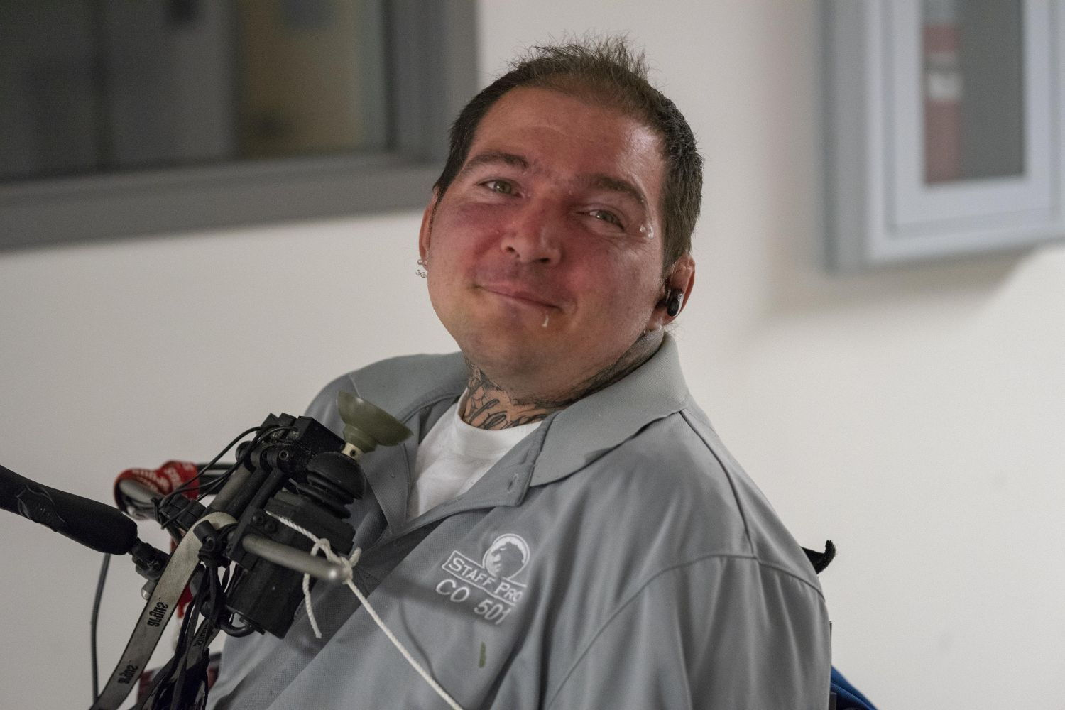 a gentleman poses with his chin control wheel chair  joystick