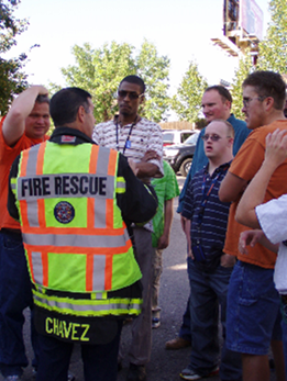 A fire rescue professional speaks with a group of people with disabilities