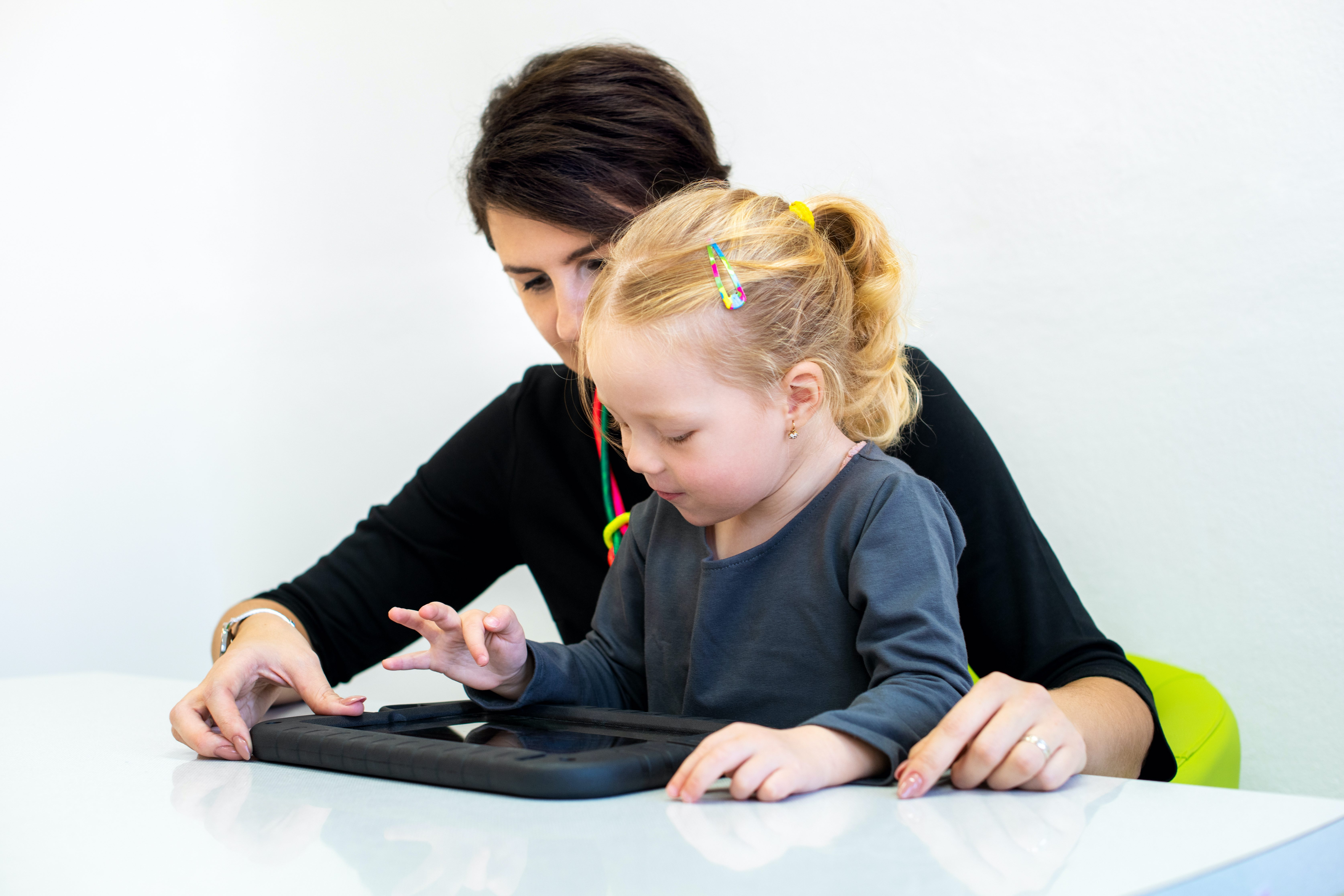 therapist using a tablet with a little girl