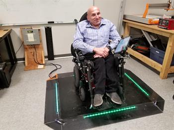 a gentleman in a wheelchair charging on a wireless charging pad