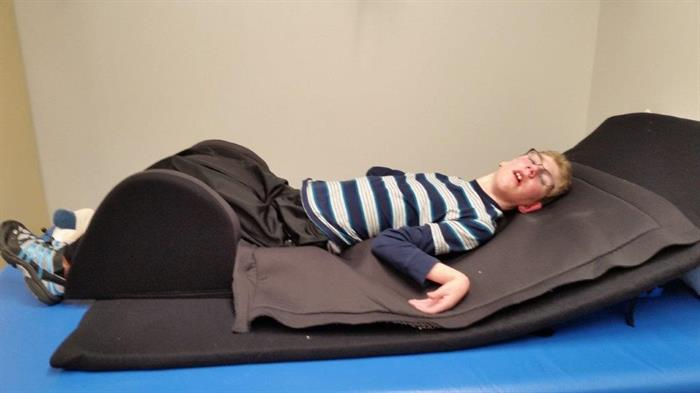 a young man with cerebral palsy lies with his legs supported on a certified sleep system mattress