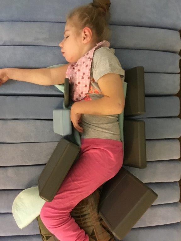 A child is supported lying on her side on a dreama mattress