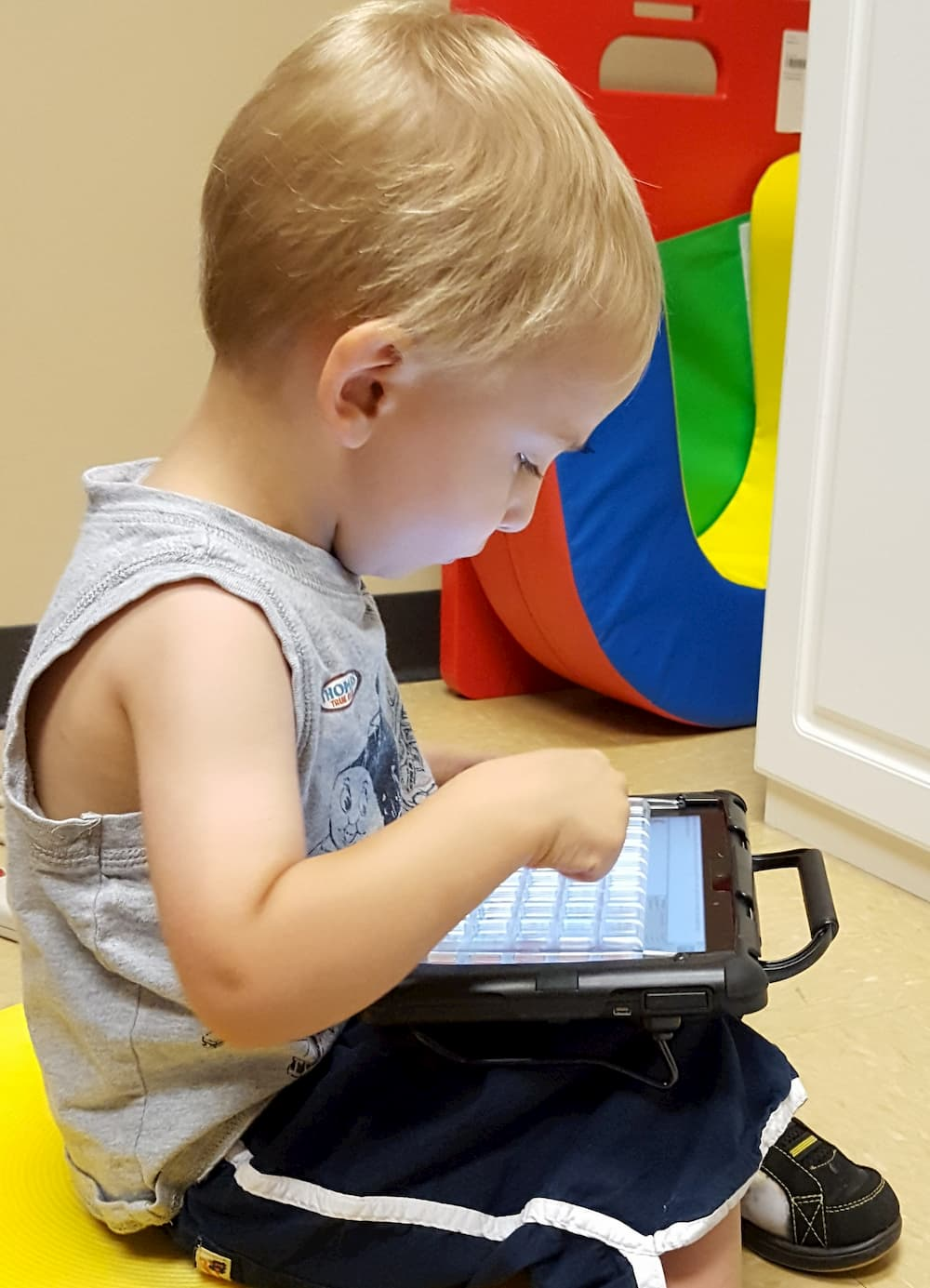 a young child uses his communication device