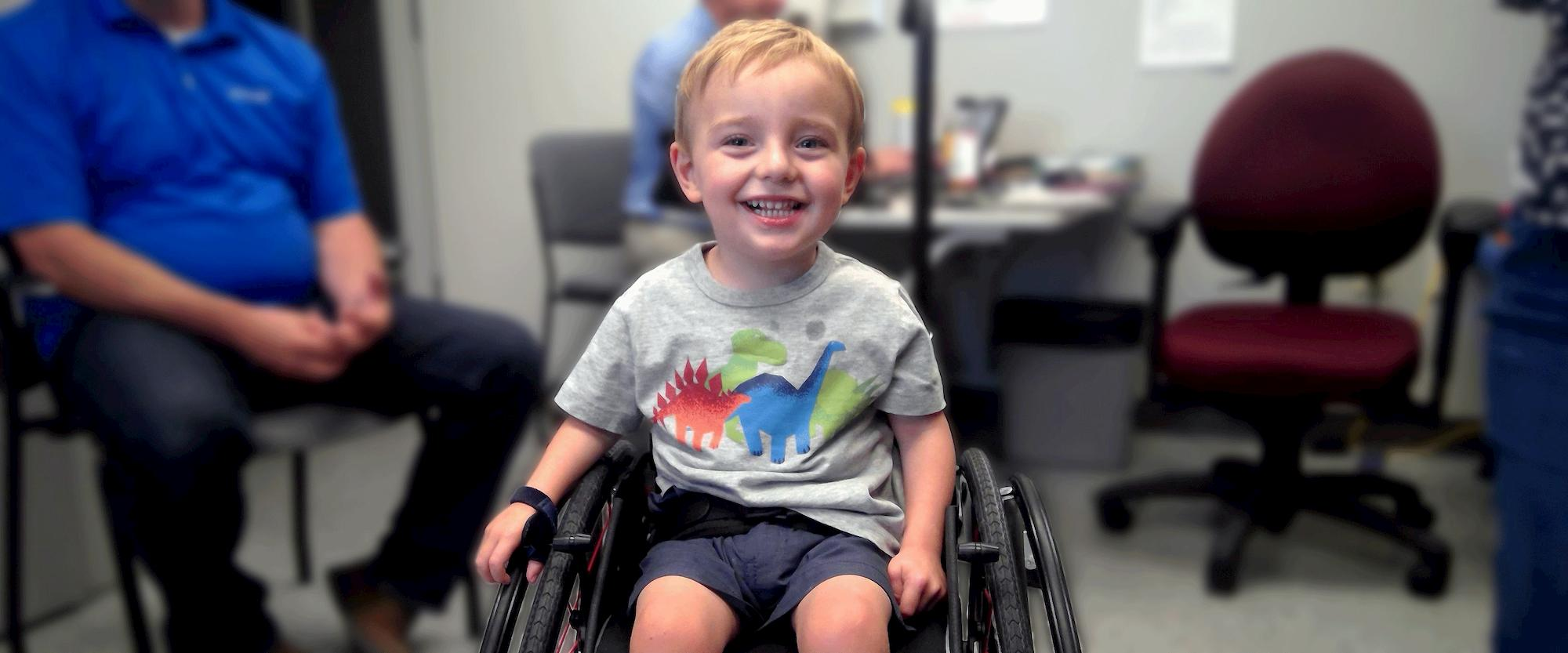 a child smiles while sitting in his wheelchair